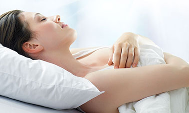 woman lying on her back with white pillow and smiling with her eyes closed