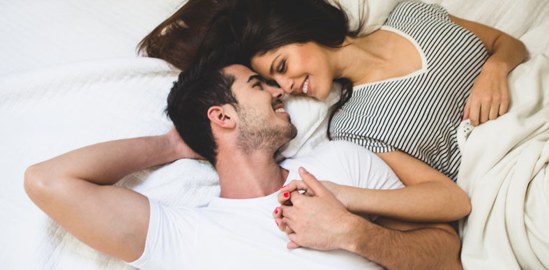 Love couple holding hands and lying in bed