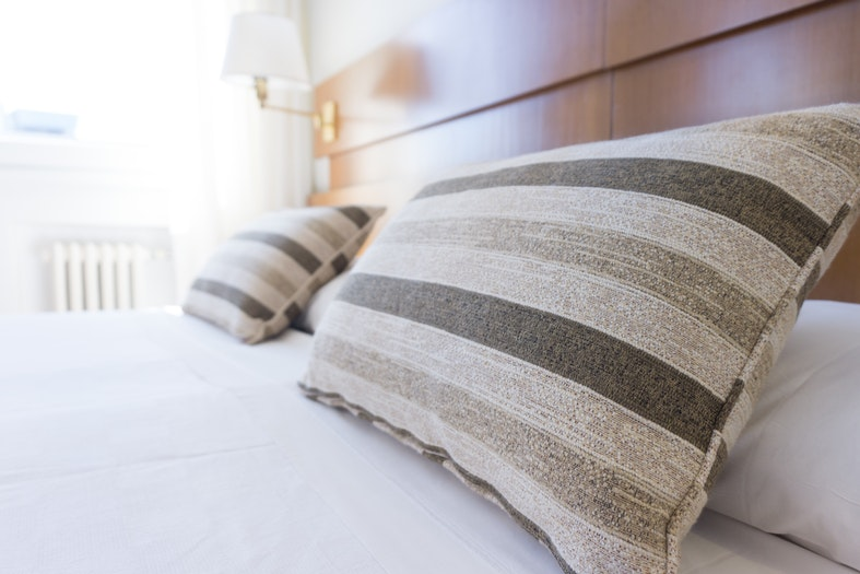 image showing decorative and sleeping pillows with white bed linen