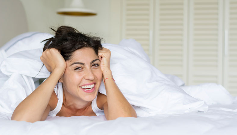 happy woman smiling in the bed
