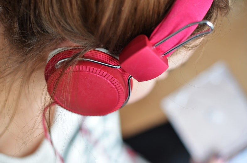 Close-up of a woman with pink headphones listening music