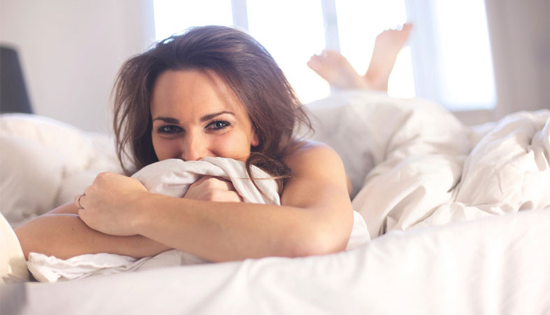image of a woman smiling in bed