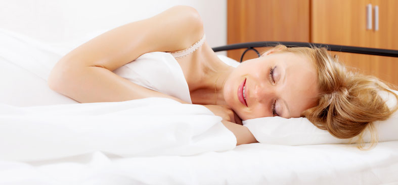 Smiling woman sleeping in her bed