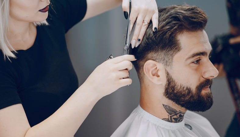 Hair stylist cuts man's hair