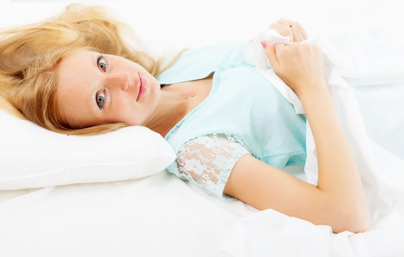 blonde woman lying on white sheet