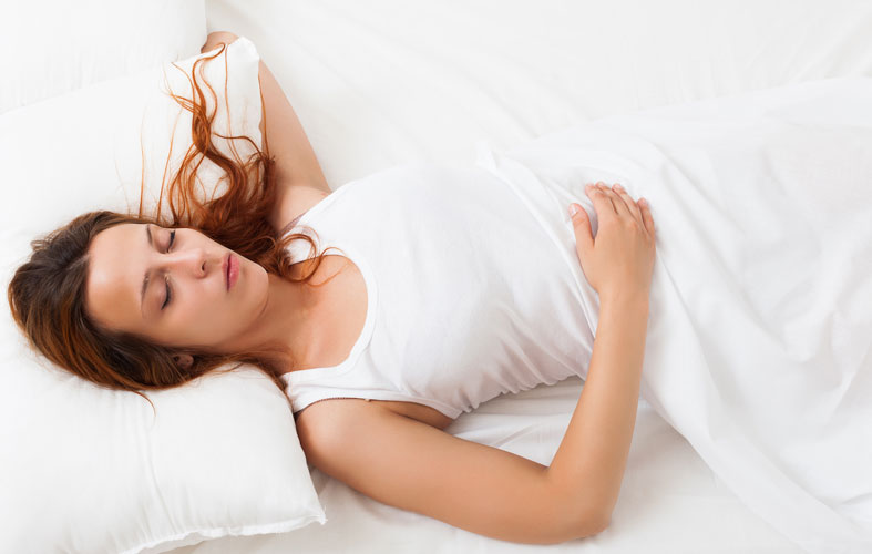 girl sleeping on a white pillow in bed at home