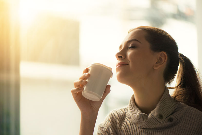 happy woman drinking her morning coffee