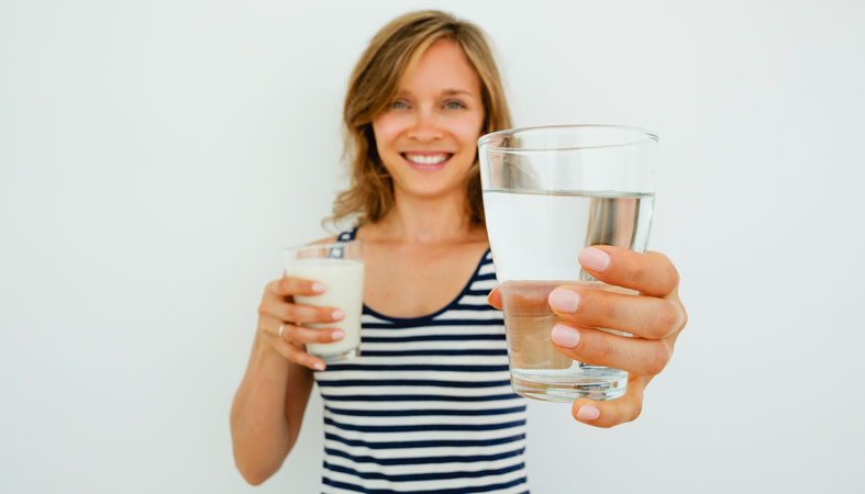 happy woman hold a glass of milk and water
