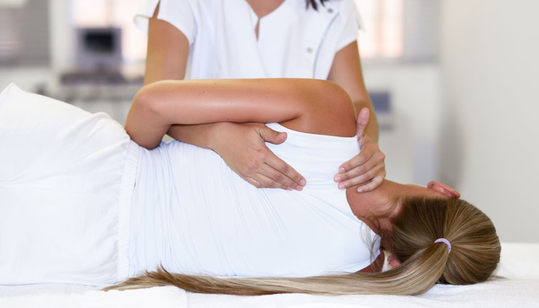 female physiotherapist giving shoulder massage to woman