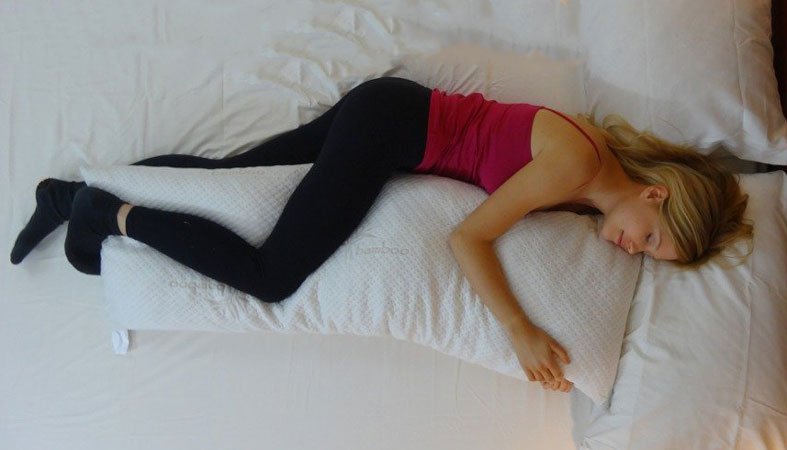 woman sleeps with a body pillow
