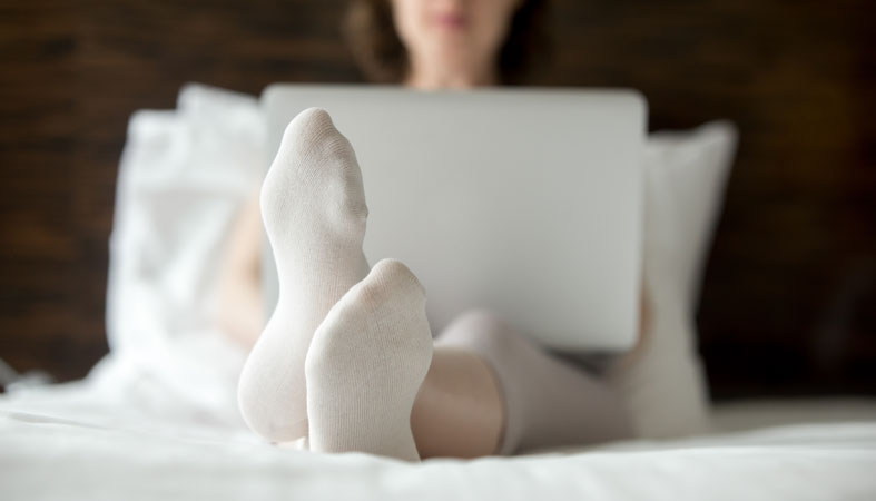 Woman is sitting on bed and wearing socks