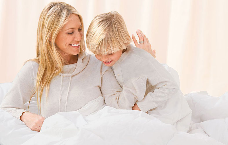 woman and child are smiling on the bed