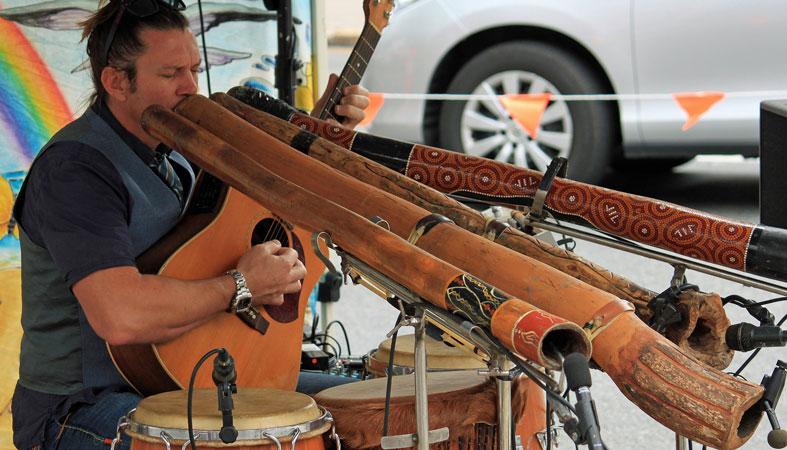 man playing didgeridoo and guitar
