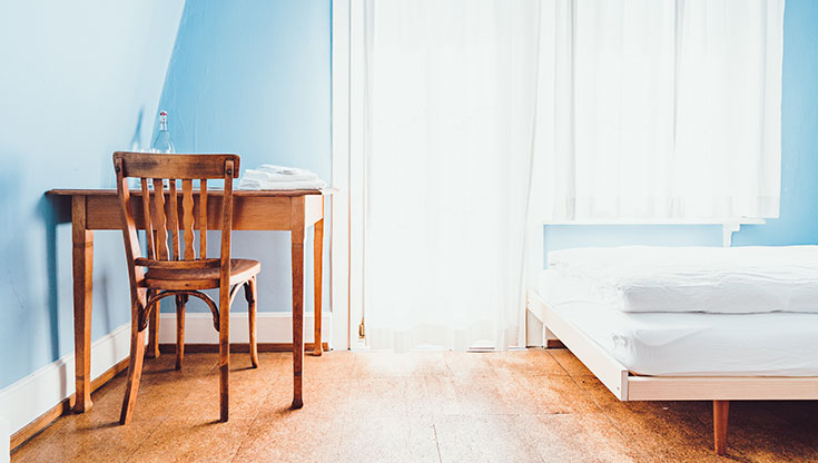 Blue bedroom with a desk and a chair from the wood