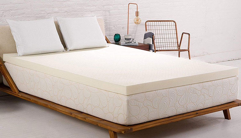 White bed with mattress topper