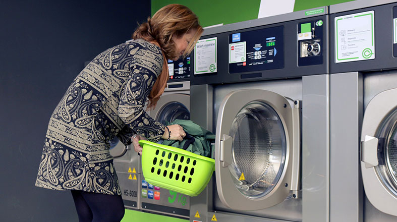 Woman is putting stuff in the washing machine