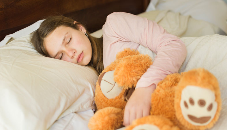 girl sleeping with teddy bear on bed