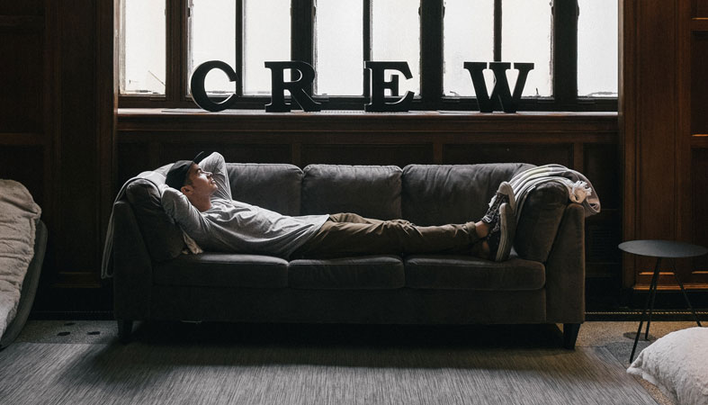 man is relaxing on sofa