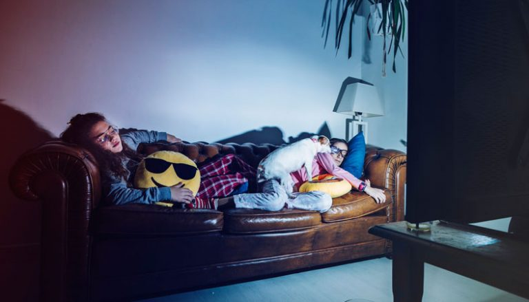two girls and a dog are napping in front of a tv