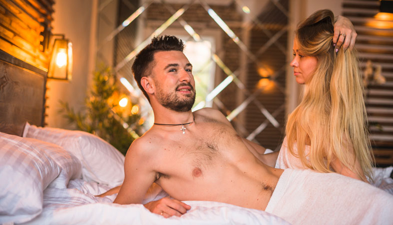 woman looking at shirtless man lying on bed