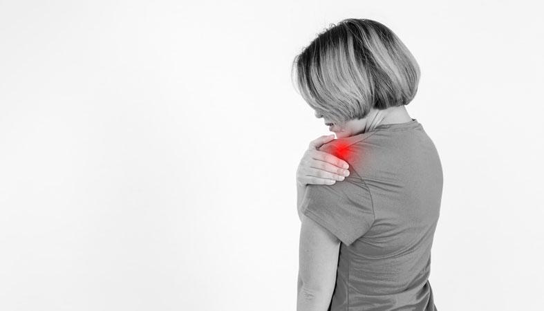 woman massaging sore shoulder