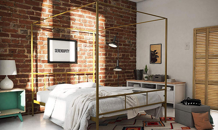 canopy bed with a golden frame and a brick wall behind it