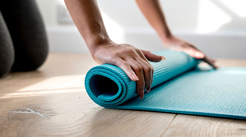 female hands are rolling in the mat for yoga