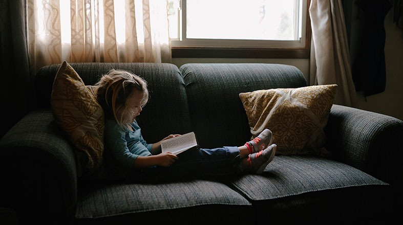 little girl is reading on the sofa