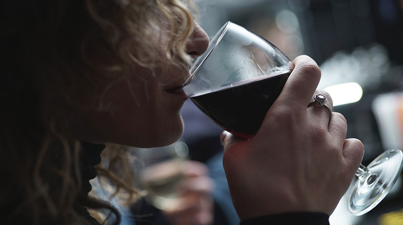 woman is drinking red wine