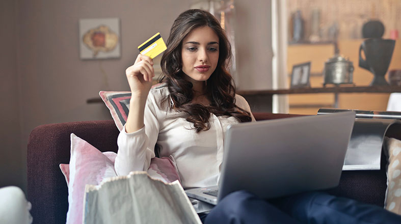 Beautiful woman is sitting on the bed and shopping online while she is holding her credit card in her right hand