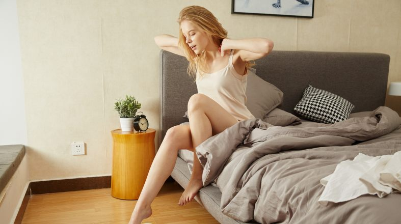 blond girl is trying to wake up while she's sitting in the bed and stretching her arms