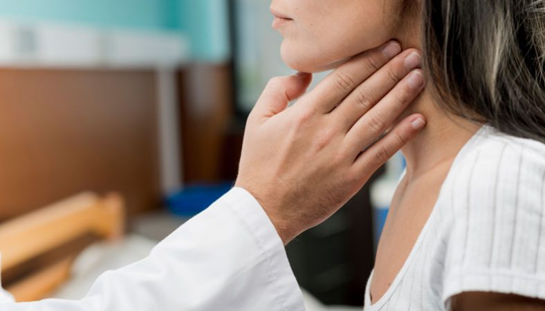doctors hand examining throat of a patient