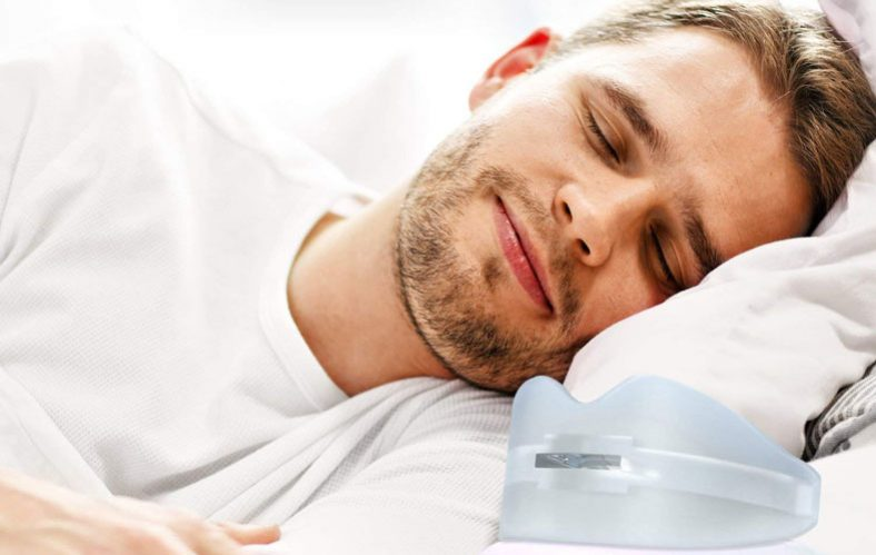 man sleeping in bed with a mouth guard next to him
