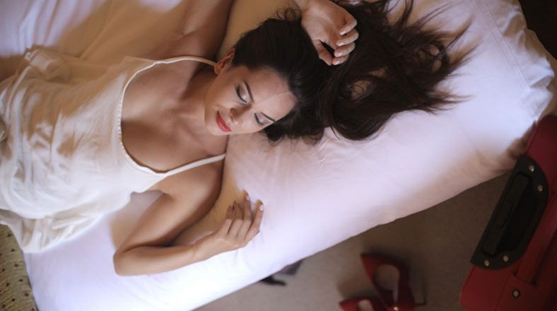 pretty woman with dark hair in white sleeping shirt is relaxing on the bed