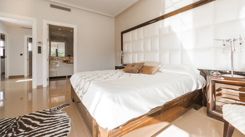 A bedroom with big white bed with brown pillows