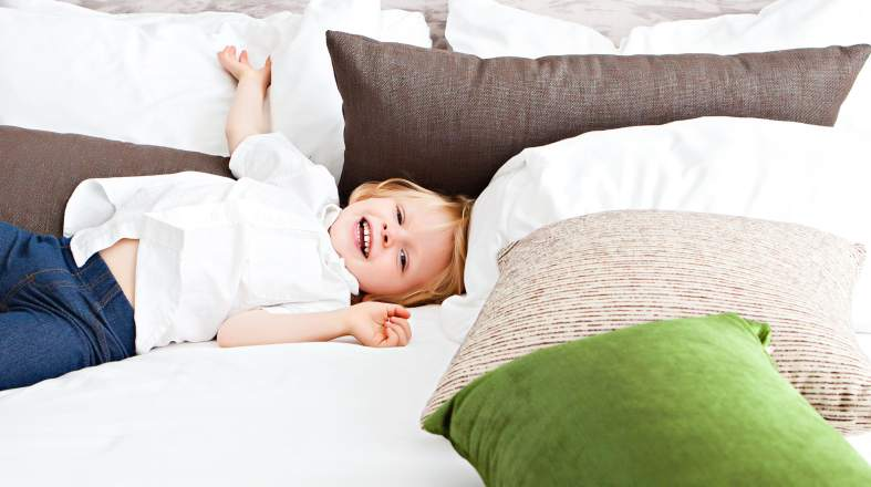 Cute toddler is laying on the bed and smiling