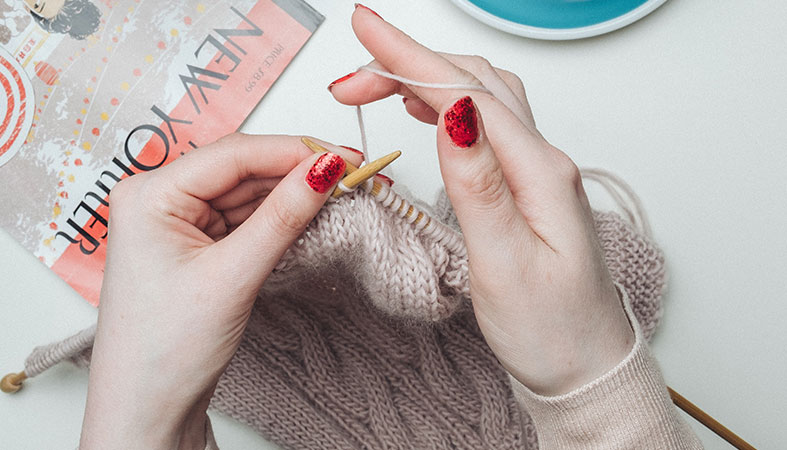 Woman's hands are knitting the clothes