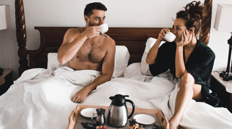 a couple is having a breakfast in the bed