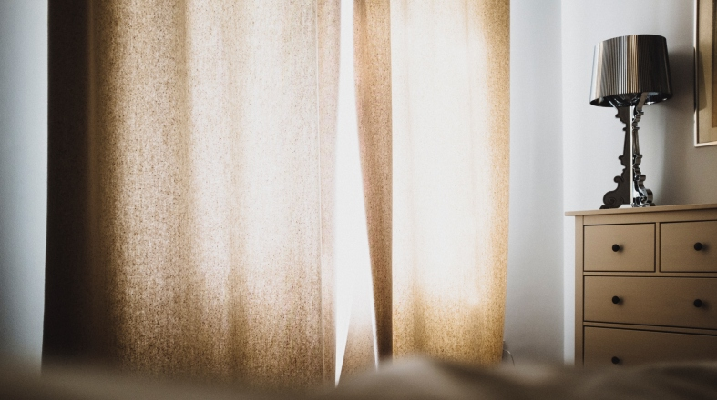 a room with beige curtains and a lamp on the small closet