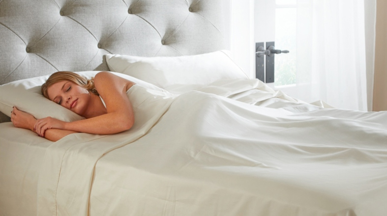 a woman is peacefully sleeping on the bed