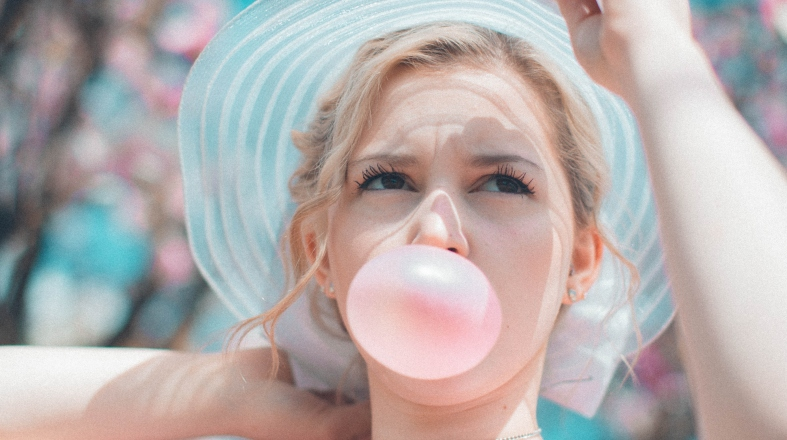 blonde woman is blowing a bubble with a gum