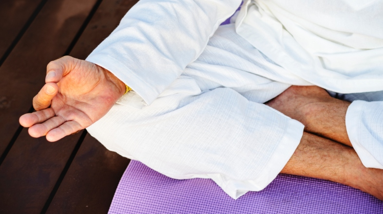 close up of man's body in meditation pose