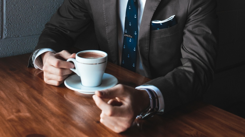 close up photo of the man with business outfit holding a cup of coffee