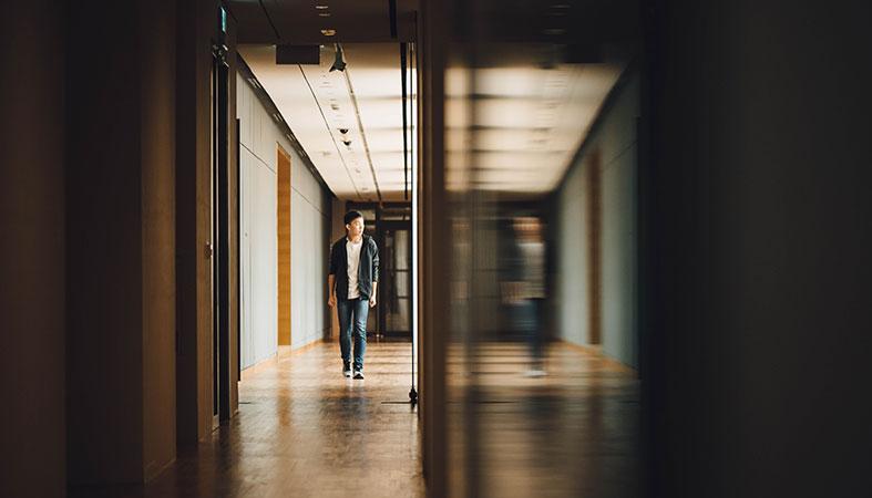 teen is walking through the empty school hall