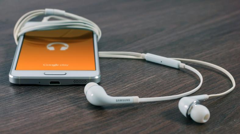 white phone with white earplugs around it