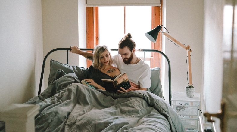 young couple is sitting on the bed and reading a book