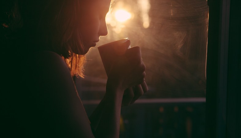 young woman is drinking tea with the sunrise in the background