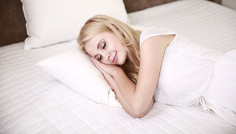 Happy woman is sleeping on the bed with a white cover