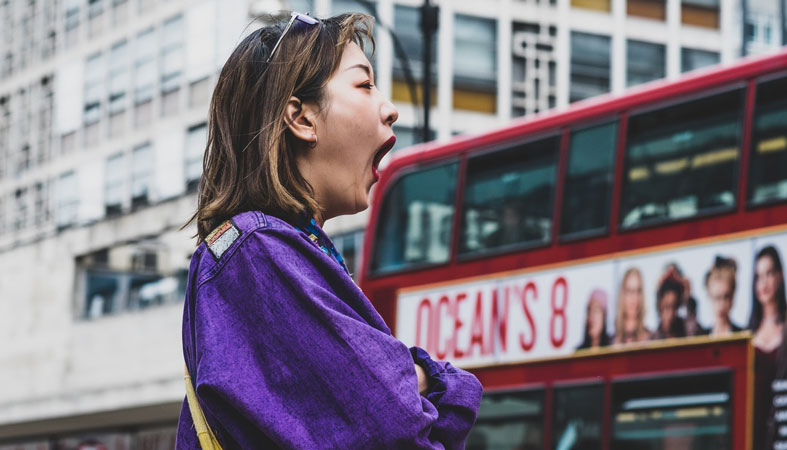 woman in purple top yawning