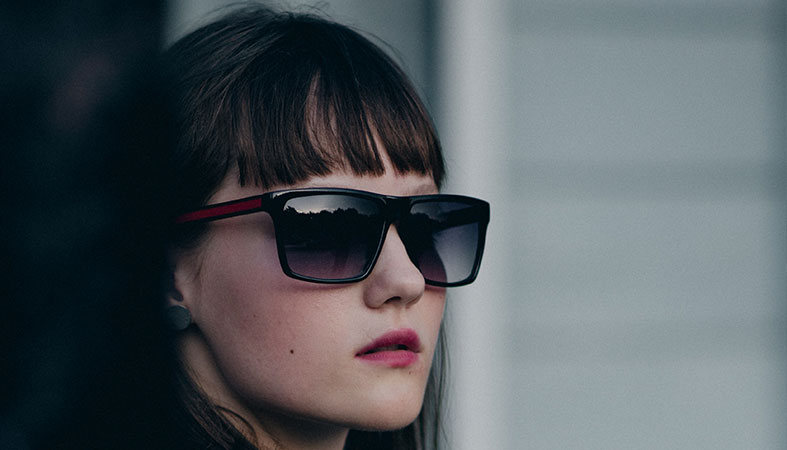 a girl is wearing black sunglasses